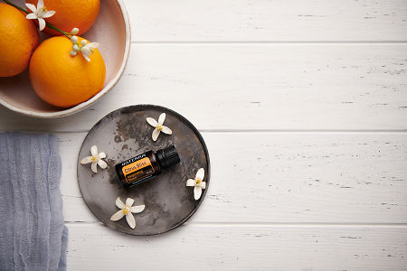 doTERRA Citrus Bliss with orange blossom flowers on a ceramic plate with a white ceramic bowl filled with seville oranges and orange blossoms on a white wooden background.