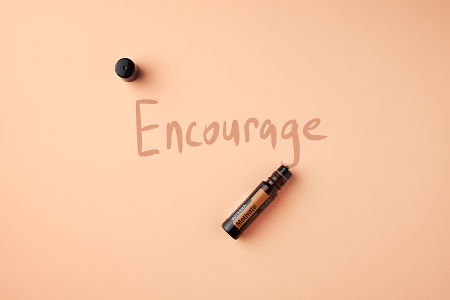 "doTERRA Motivate Touch on a light salmon colored background with handwritten ""Encourage"""