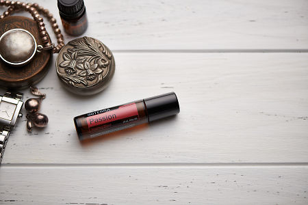 doTERRA Passion Touch blend, jewellery and trinkets on white rustic wooden background.