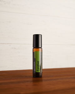 doTERRA Forgive Touch on a brown wooden side table.