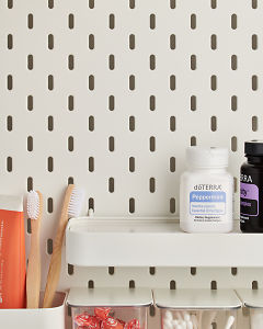doTERRA Peppermint Softgels on a bathroom shelf with additional doTERRA products and bathroom accessories.