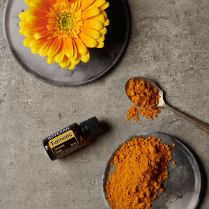 doTERRA Turmeric, ground turmeric on a ceramic plate, a yellow flower on a ceramic plate and turmeric in a teaspoon on a grey stone background.