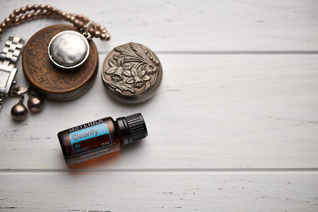 doTERRA Clearify blend, jewellery and trinkets on white rustic wooden background.