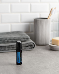 doTERRA Ice Blue Roll On with bathroom acessories on a bathroom bench top.