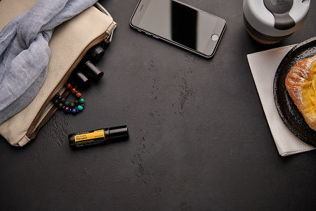 doTERRA Manuka Touch with a leather clutch, roller bottles, cell phone, coffee and food on a black background.