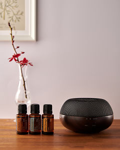 doTERRA Brevi Walnut diffuser with Cassia, Siberian Fir and Wild Orange essential oils on a side table.