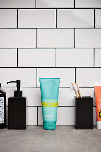 doTERRA Spa Hand and Body Lotion with bathroom accessories on a stone bathroom benchtop.