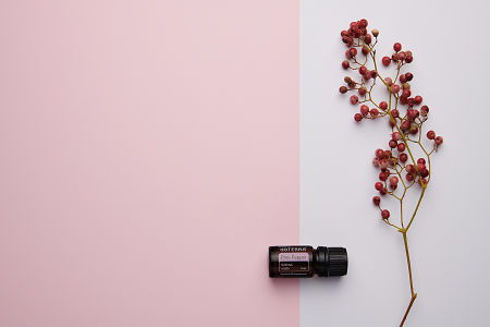doTERRA Pink Pepper and pink peppercorn branch on a pink and white background.