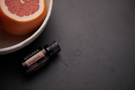 doTERRA Grapefruit oil and fruit in white ceramic bowl on black background.
