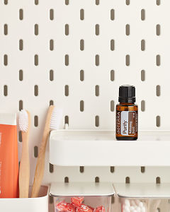 doTERRA Purify Refreshing Blend on a bathroom shelf with additional doTERRA products and bathroom accessories.