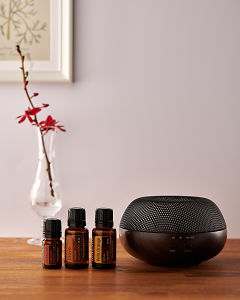 doTERRA Brevi Walnut diffuser with Cinnamon, Clove and Wild Orange essential oils on a side table.