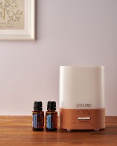 doTERRA Lumo diffuser with Peppermint and Ylang Ylang essential oils on a side table.