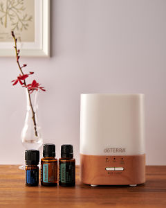 doTERRA Lumo diffuser with Deep Blue, AromaTouch and Balance essential oils on a side table.