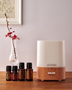 doTERRA Lumo diffuser with Cardamom, Cinnamon, Clove and Wild Orange essential oils on a side table.