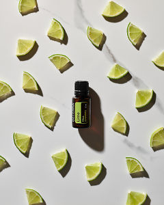 doTERRA Lime essential oil and slices of lime scattered on a white marble background.