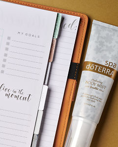 doTERRA Spa Hydrating Body Mist with Beautiful Blend and an open journal with an inspirational quote on a gold background.
