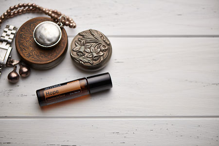 doTERRA Hope Touch blend, jewellery and trinkets on white rustic wooden background.