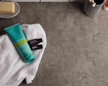 doTERRA Spa Hand and Body Lotion with Lavender and Roman Chamomile essential oils and bathroom accessories on a white towel on a stone background.