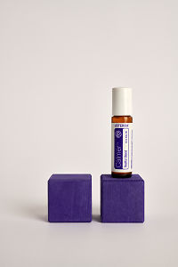 doTERRA Kids Oil Collection roll-on bottle Calmer on a purple wooden block.