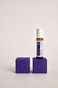 doTERRA Kids Oil Collection roll-on bottle Calmer on a purple wooden block.