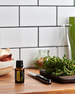 doTERRA Thyme on a kitchen bench with fresh thyme.
