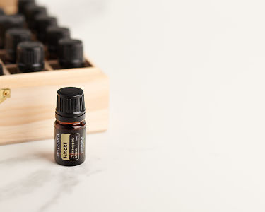 doTERRA Hinoki in front of an essential oil box on a white marble bench.