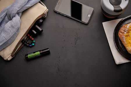 doTERRA Melaleuca Touch with a leather clutch, roller bottles, cell phone, coffee and food on a black background.