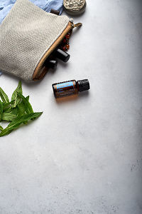 doTERRA Easy Air with clutch, accessories and mint leaves on a white concrete background.