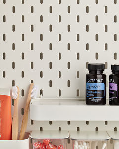 doTERRA DigestZen Softgels on a bathroom shelf with additional doTERRA products and bathroom accessories.