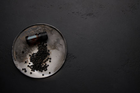 doTERRA Black Pepper and black peppercorns on a ceramic plate with a black concrete background.