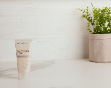 doTERRA Essential Skin Care Invigorating Scrub on a white marble bench with a pot plant.
