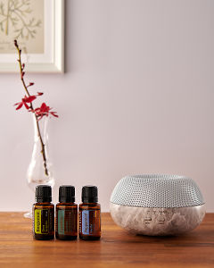 doTERRA Brevi Stone diffuser with Bergamot, Cypress and Peppermint essential oils on a side table.