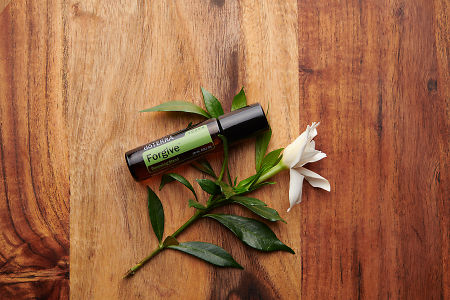 doTERRA Forgive Touch with a white flower on a brown wooden background.