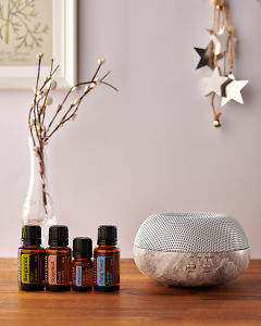 doTERRA Brevi Stone diffuser with Bergamot, Grapefruit, Juniper Berry and Ylang Ylang essential oils and holiday decorations on a side table.