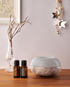 doTERRA Brevi Stone diffuser with Citrus Bliss and Spearmint essential oils and holiday decorations on a side table.