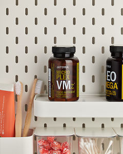 doTERRA Microplex VMz on a bathroom shelf with additional doTERRA products and bathroom accessories.