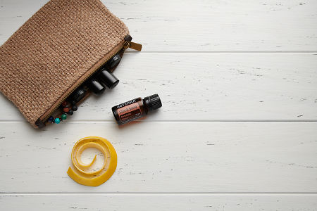 doTERRA Slim and Sassy, lemon peel and clutch with oils on white wooden background.