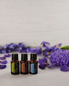 doTERRA Bergamot, Frankincense and Ylang Ylang with scattered purple flowers on white.