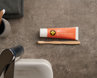 doTERRA On Guard Natural Cleansing Toothpaste and toothbrush with toothpaste on a bathroom vanity.