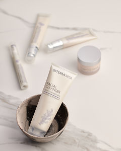 doTERRA Facial Cleanser in a ceramic bowl with other Essential Skin Care products in the background on a white marble background.