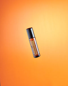 doTERRA Motivate Touch floating on a orange background.