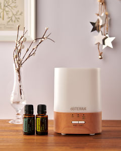 doTERRA Lumo diffuser with Balance and Bergamot essential oils and holiday decorations on a side table.