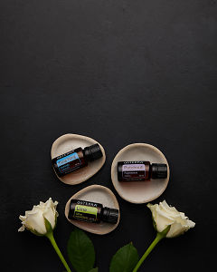 doTERRA Ylang Ylang, Patchouli and Lime in individual tiny stone dishes with white roses on a black concrete background.