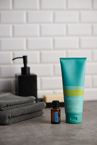 doTERRA Spa Hand and Body Lotion and Ylang Ylang essential oil with bathroom accessories on stone bench