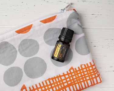 doTERRA Ascend in close up on an essential oil bag on a white wooden background.