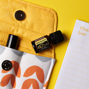 doTERRA Yellow Mandarin on an essential oil bag and a check list on a yellow textured background.