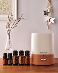 doTERRA Lumo diffuser with Cinnamon, Douglas Fir, Citrus Bliss, Lemon and Wild Orange essential oils and holiday decorations on a side table.