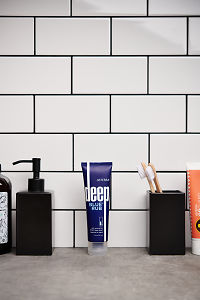 doTERRA  Deep Blue Rub with bathroom accessories on a stone bathroom benchtop.