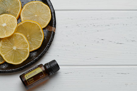 doTERRA Lemon oil and slices on black ceramic plate with white rustic wooden background.