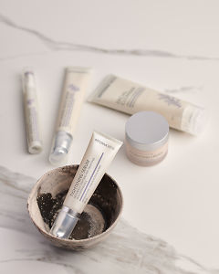 doTERRA Tightening Serum in a ceramic bowl with other Essential Skin Care products in the background on a white marble background.